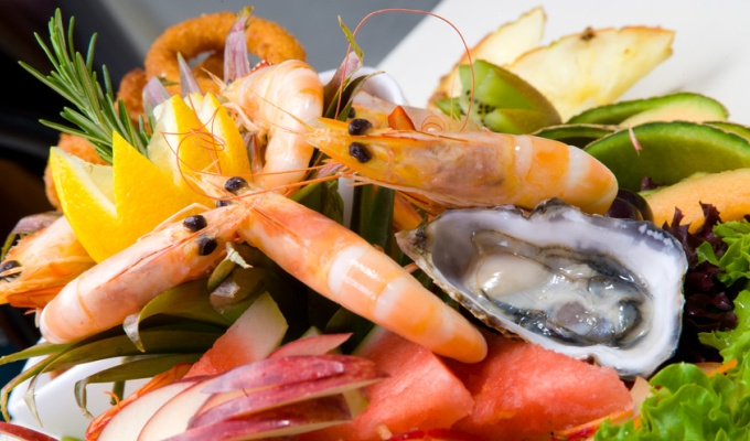 Seafood platter served fresh and deep fried surrounded with salad and fruit